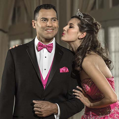 Woman wearing a pink dress kissing a man in black tuxedo on the cheek